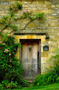 A quintessential English stone cottage with climbing roses, Castle Combe, near Bath, England