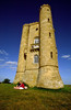 A couple picnics beneath Broadway Tower, built on the whim of the Earl of Coventry for his Countess, near Broadway, the Cotswolds, England.