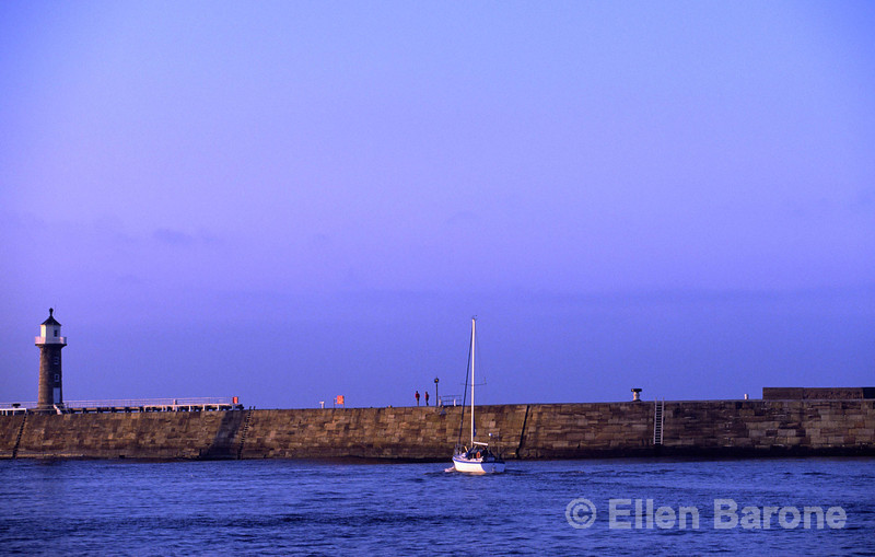 A lone sailboat enjoys a magical evening in Whitby harbour, Whitby Lighthouse, Whitby, Yorkshire, England.