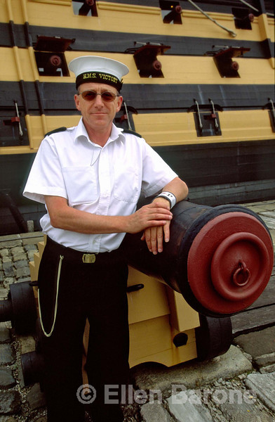 A friendly sailor greets visitors aboard the HMS Victory, the English flagship on which Admiral Nelson was killed at the Battle of Trafalgar, Royal Naval Museum, historic dockyards, Victorygate, Portsmouth, England.