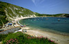 Sheltered Lulworth cove is almost encircled by white cliffs, Isle of Purbeck (which is in fact a peninsula), Dorset Coast, England.
