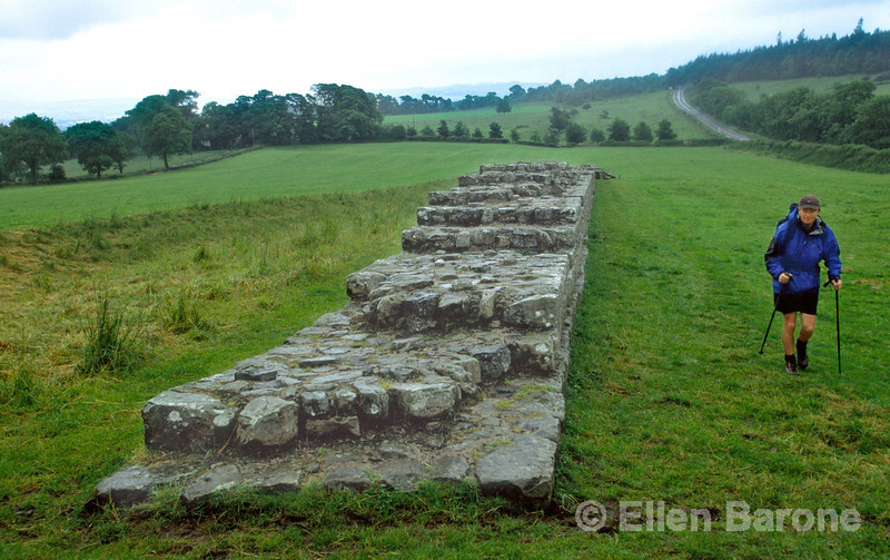 Hiker, the crumbled remains of Hadrian's Wall (AD 120),  a 73 mile (117 km) wall erected across northern England to defend the northern limits of the Roman Empire, NorthUmbria, England.