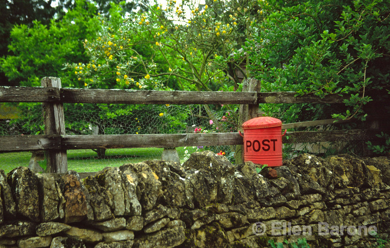 Rural private post box sits atop a dry stone wall, the Cotswolds, England