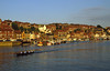Rowers, a crew boat practices on the River Esk that divides the picturesque town of Whitby, Yorkshire, England.