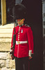 Dressed in brilliant scarlet tunic and tall furry hat (called bearskins) a Palace Guard stands sentry outside Buckingham Palace, London, England.