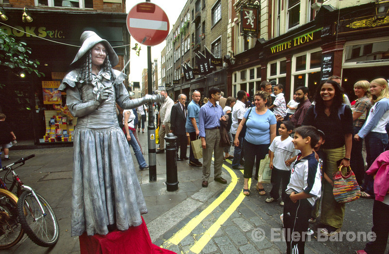 A street performer entertains a crowd at lively Covent Garden, London, England.