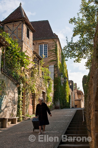 Street scene, old woman with market bag, Sarlat, France.