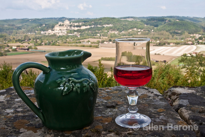 Traditional wine pitcher and glass of rose, with a view of Beynac in the distance, as viewed from Chateau Marquayssac, Dordogne, France.