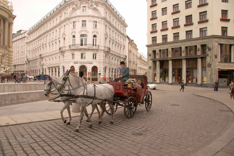 Traditional horse-drawn fiacres (open carriages) are a popular way to tour the Altstadt (Old City) , Michaelerplatz, Vienna, Austria, Europe.