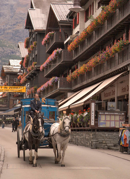 Horse and carriages transport visitors in the car-free alpine village of Zermatt, Switzerland, Europe.