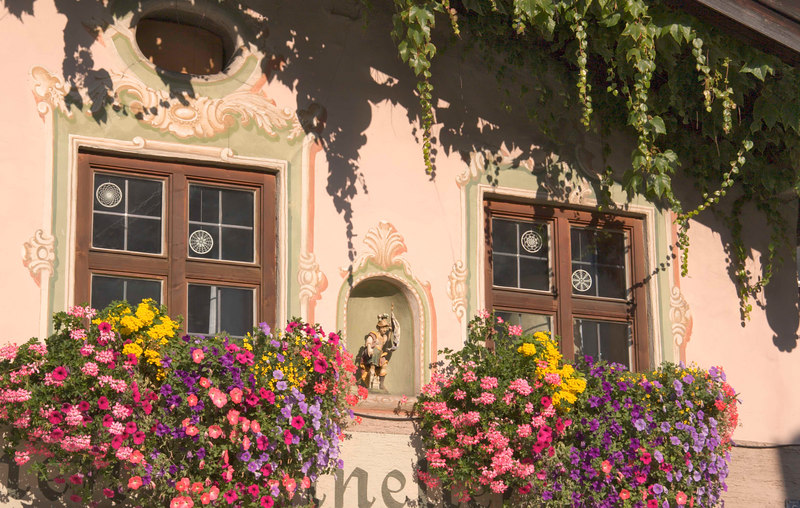 Storybook painted houses and flowerbox windows bursting with color are typical of lovely Obergammergau, Bavaria, Germany, Europe.