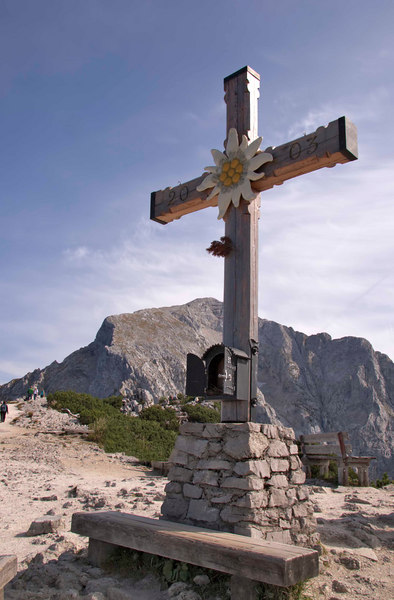 A wooden cross stands atop the Hoher Goll, a peak in the Bavarian Alps, near the Kehlstein, or Eagle's Nest (background). The cross was erected in 1951. Bavaria, Germany, Europe.