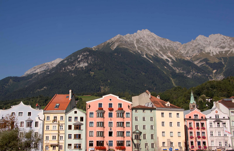 The dramatic mountain backdrop and colorful architecture along the River Inn, Innsbruck, Tyrol, Austria, Europe.