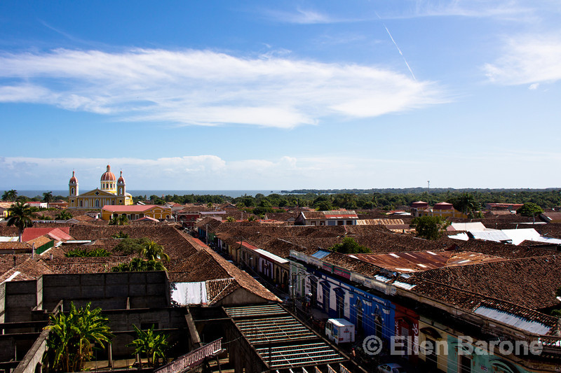 Red tile roofs, colorful houses, church steeples, Lake Nicaragua in the distance, as viewed from La Merced bell tower, Granada, Nicaragua.