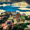 Brightly painted houses cling to the steep hillsides of Guanajuato, Mexico.