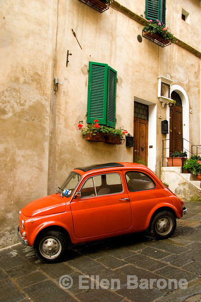 a colorful Fiat parked on a steep steet in the picturesque hilltop town of Montepulciano, Umbria, Italy
