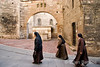 habit-clad nuns wander past an ancient well hidden among a maze of  narrow medieval lanes, Perugia, Umbria, Italy