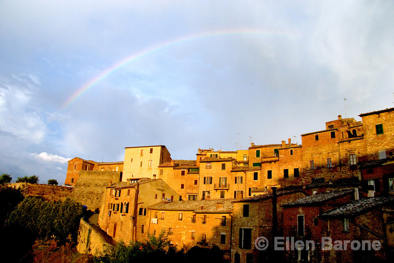 a sudden rainbow radiates above the honey colored hilltop skyline of Montepulciano, Umbria, Italy
