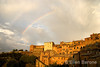 a double rainbow radiates above the honey colored hilltop skyline of Montepulciano, Tuscany, Italy