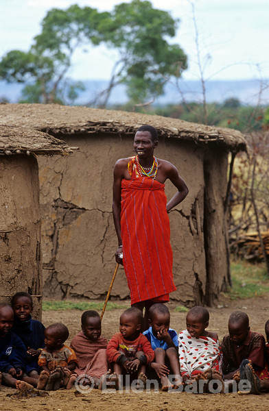 Maasai warrior with children, traditional Masai village, Masai Mara National Reserve, Kenya, East Africa.