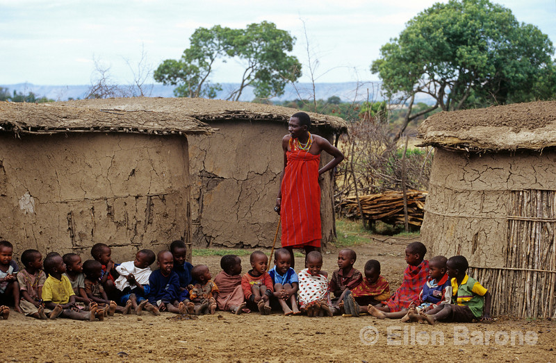 Massai warrior with children, traditional Masai village, Masai Mara National Reserve, Kenya, East Africa.
