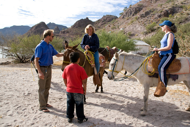 Safari Quest first mate, Dirk Boshckek, and a local youngster help passengers Jane DuFour and Paula Schrader prepare for a burro ride in Puerto Agua Verde, Sea of Cortez, Baja California Sur, Mexico.