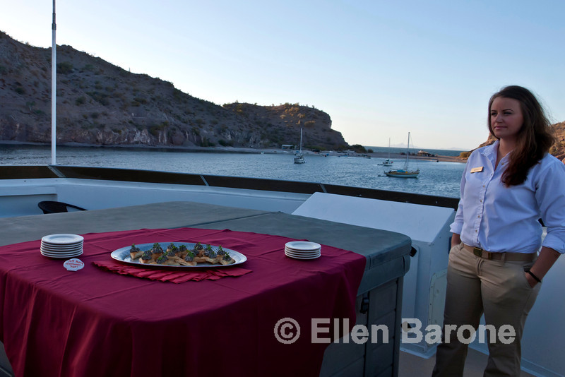 Safari Quest steward, Nicole Bitz, sets out evening appetizers using the top deck hot tub as an impromptu table, Sea of Cortez, Baja California, Mexico.