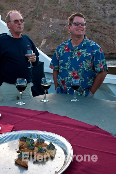 Safari Quest passengers Mike Medema and Allan Smith enjoy evening cocktail hour on the top deck, Sea of Cortez, Baja California, Mexico.