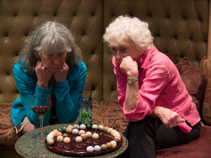 Passengers Paula Schrader and Irene Wicklund engrossed in an evening board game aboard Safari Quest, Sea of Cortez, Baja California Sur, Mexico.