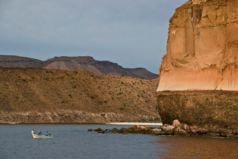 A local fishing boat is dwarfed beneath towering red cliffs, Sea of Cortez, Baja California Sur, Mexico.