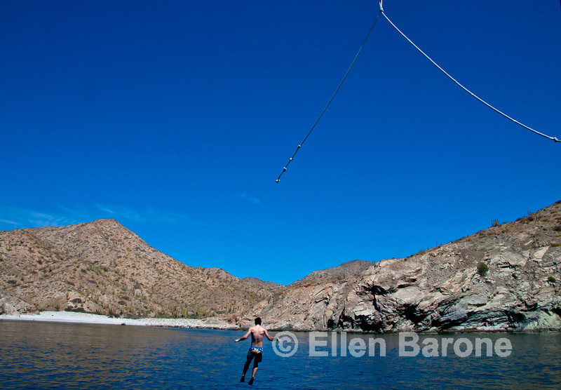 Safari Quest passenger Kirk Mauro enjoys the ship's rope swing, Sea of Cortez, Baja California, Mexico.