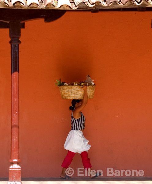 Woman vendor carrying basket on head, Granada, Nicaragua, Central America.