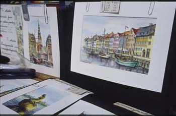 A local artist offers visitors original wtercolors of Lille Havfrue (the Little Mermaid) along the quay of Lingelinie, Copenhagen, Denmark