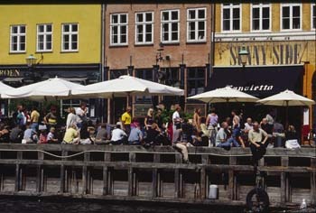 Visitors and locals alike flock to Nyhavn (New Harbor), a colorful, bustling wharf in Copenhagen, Denmark