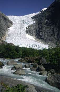 A great cascade of ice at the Bridsdals glacier hangs above the ice flows and glacier lake near Leon, Norway