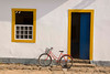 A bicycle rests perched against a wall in cheefully colorful  colonial Parati, a UNESCO World Heritage community, Brasil. ©2007 Ellen Barone.