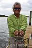 Outside Hilton Head guide, Captain Mike Pace, demonstrates the proper way to hold a live crab, Page Island, Hilton Head Island, South Carolina, USA, North America.