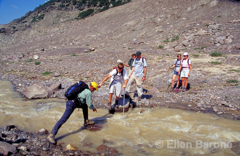 Guide Thierry Cardon helps hiker across a stream, Canadian Mountain Holidays, Helihiking, Bobbie Burns Lodge, Purcell Mountains, British Columbia, Canada