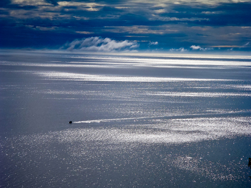 A solitary boat in Kachemak Bay as viewed from the Bear's Den Lodge, Alaska Adventure Cabins, Homer, Alaska.