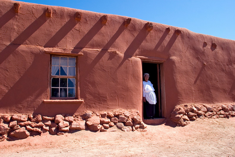 Woman in doorway, El Rancho de las Golondrinas is a 200-acre living history museum near Santa Fe, NM.