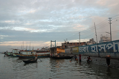 "Early morning sunrise over Buriganga River (Bangla: বুড়িগঙ্গা Buŗigônga ""Old Ganges"") as the men brush their teeth, bathe and wash themself in the river water.  Don't miss the tooth brush on the floor which the person soaps himself! Buriganga is the life line and much happens in and around this river. It is the main river flowing beside Dhaka, capital cityof Bangladesh. With an average depth of 39 feet (12 m) its quite amazing to see the activities along the river. Unfortunately, the river is Dhaka's main outlet of sewage waste and is threatened by pollution and waste. What was mind boggling was that people were using this mucky water to drink, gargle, brush their teeth and take bath all within feets of each other! Amazing immunity system! Dhaka, Bangaladesh"