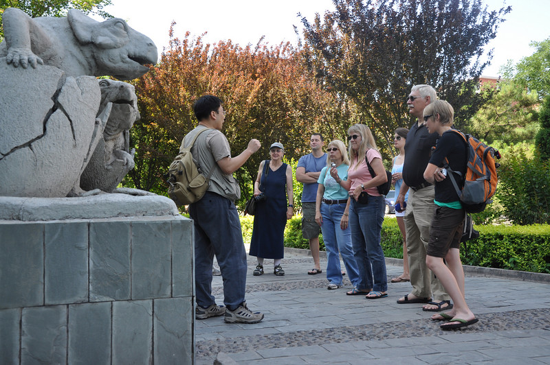 "Here's Hailu telling the group about the IVPP and its history.  He actually got his start there, way back when...  The cement sculpture is of two ostensibly baby <i>Protoceratops</i> emerging from eggs, which they undoubtedly did, but the idea represents an outmoded idea that eggs discovered by <a href=""http://www.roychapmanandrewssociety.org/who_was.html"">Roy Chapman Andrews</a> and <a href=""http://users.rcn.com/granger.nh.ultranet/"">Walter Granger</a> (from the <a href=""http://www.amnh.org/"">American Museum of Natural History</a> in New York) in Mongolia actually belonged to <i>Protoceratops</i>.  These eggs have since been shown to belong to theropod dinosaurs, specifically oviraptorosaurs -- more details <a href=""http://en.wikipedia.org/wiki/Citipati"">here</a>."