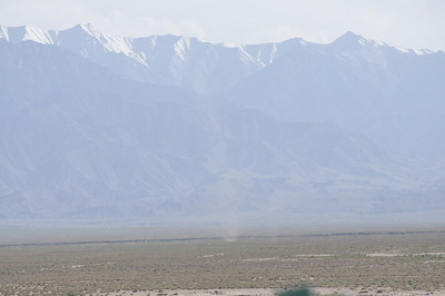 A dust devil on the alluvial plain in front of the mountains.