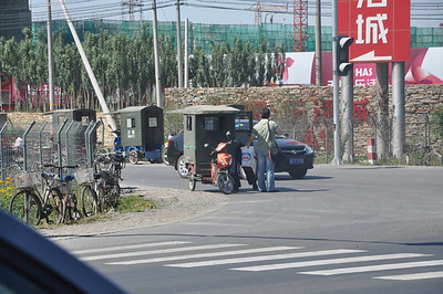 This is what a modern-day rickshaw looks like -- fares ride in the little housing thing.  All motorized, of course, although a few bicycle-driven ones are still around.