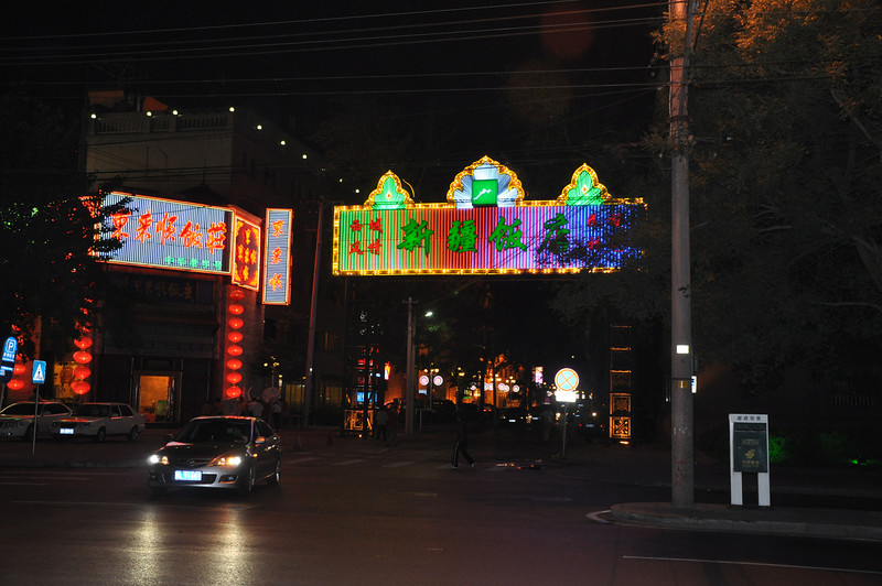 The Xinjiang Hotel's front all lit up at night.