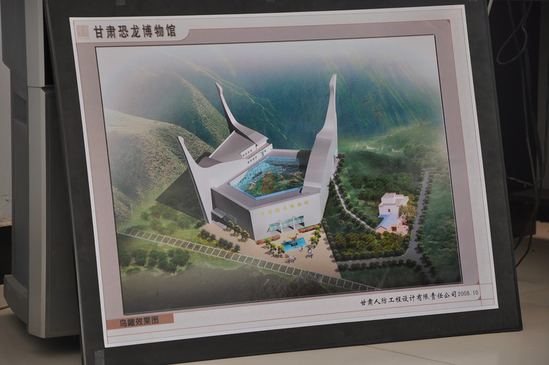 We had a surprise down at the office building: a new museum, the future Gansu DInosaur Museum, is going to be built behind the office building, at the base of the hill on which the track site is located.  In this schematic of the new museum (the huge, three-spired building -- BTW, the spires are stylized sauropod necks and heads!), the office building is the puny thing to the right...and it's a big building in its own right!  Eventually, mounts of Da-qing's dinosaurs will end up in this museum.  Combined with the track site, this will make Liujiaxia a dinosaurian mecca!