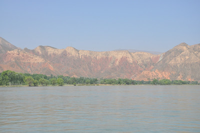 On the boat ride, we go past many spectacular outcrops -- as before, the reddish, Lower Cretaceous Hekou Group below and whitish Cenozoic strata on top.  Here's one of the views near the starting point.  It's a bit hazy because of the outpourings from the Lanzhou city factories...