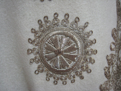 Detail of the handworked embroidery on one of the gowns on display.