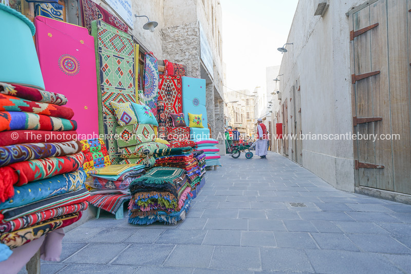 Man in traditional atire with wheelbarrow in lane of Souq Waqif markets just beyond a colorful rug and carpet display.