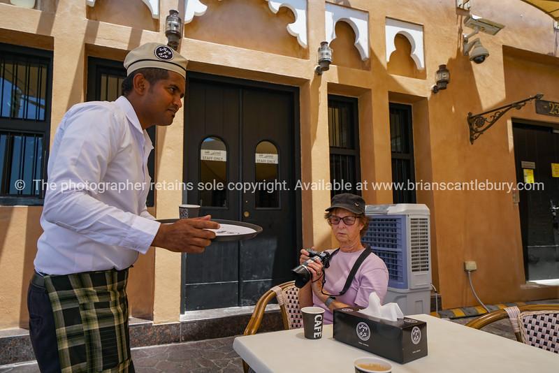 Waiter serving traditional  coffee drink known a karak in Katara Cultural Village